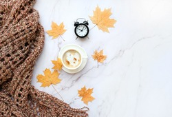 coffee Cup, alarm clock, autumn leaves and scarf on marble background. atmosphere cozy autumn composition. fall season concept. copy space