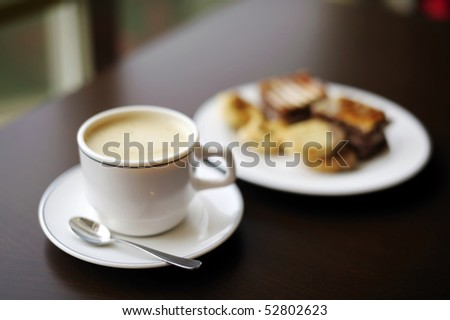 Coffee cup and a plate with cookies on a background