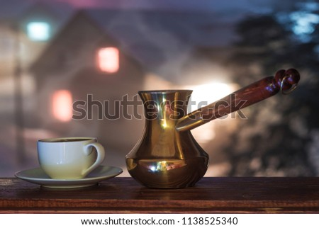 Coffee cup and coffe pot on window.