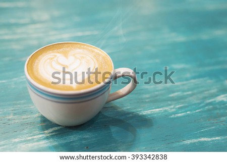 coffee cup and coffee beans.Coffee cup and coffee beans on a wooden table and sack background,Vintage color tone