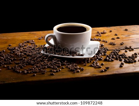 coffee cup and coffee beans on dark background