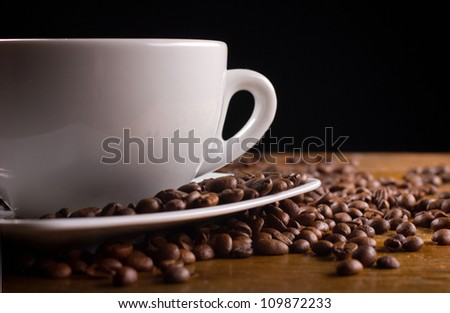coffee cup and coffee beans on dark background, closeup view - stock photo