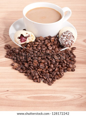 Coffee cup and coffee beans, sweets on the wooden background.