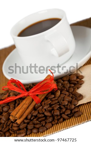 Coffee cup and coffee crops placed on bamboo coaster.