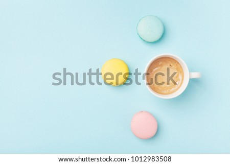 Coffee cup and colorful macaron on pastel blue background top view. Cozy morning breakfast. Fashion flat lay style. Sweet macaroons. #1012983508