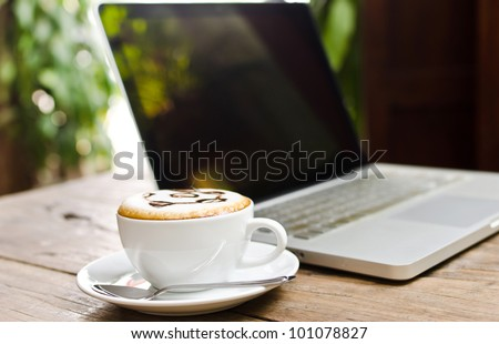 Coffee cup and laptop for business, Selective focus on coffee.
