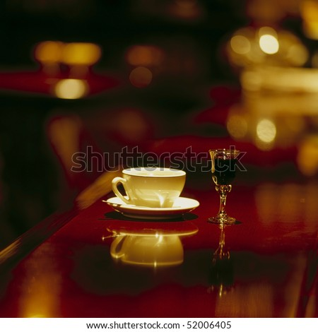 coffee cup and liquor glass in a classic wooden bar desk, selective focus, space for copy