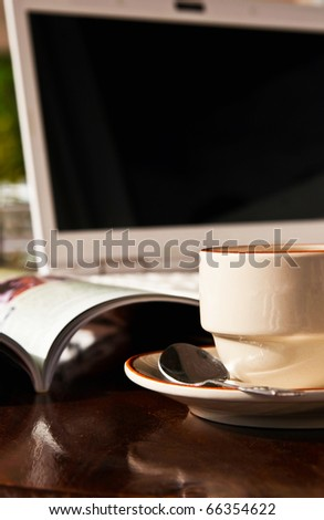 Coffee cup and notebook on wooden table