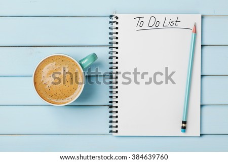 Coffee cup and notebook with to do list on blue rustic desk from above, planning and design concept Foto d'archivio ©