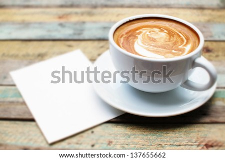 Coffee cup and paper on grunge background