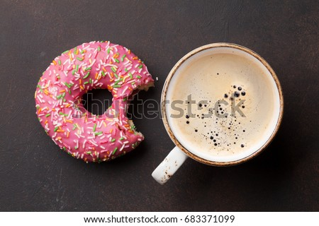 Coffee cup and pink donut on stone table. Top view