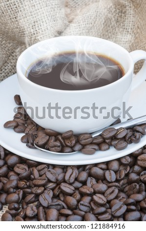 Coffee cup and saucer on hessian cloth surrounded by coffee beans