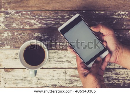 Coffee cup and smartphone on wooden table. View from above #406340305