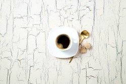 Coffee cup and spoon, sugar on old kitchen table. Top view with copy space