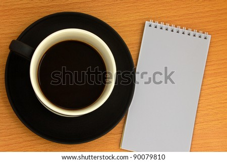 Coffee cup and white notebook