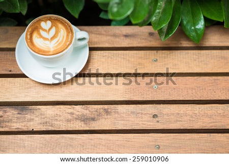Coffee cup art tree face on wood table with green leave frame, Coffee art
