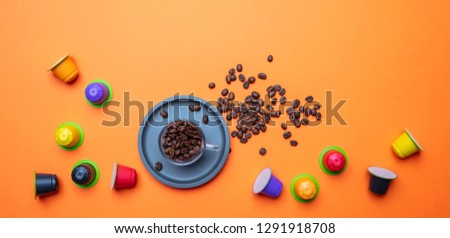 Coffee cup, beans and capsules, pods, on bright orange color background, copy space, top view Сток-фото ©