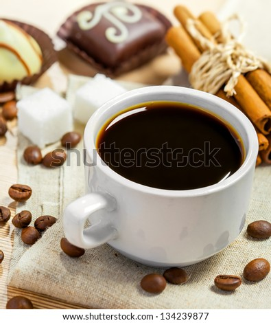 Coffee cup, beans, chocolate candy, cinnamon, sugar and anise on a table - stock photo
