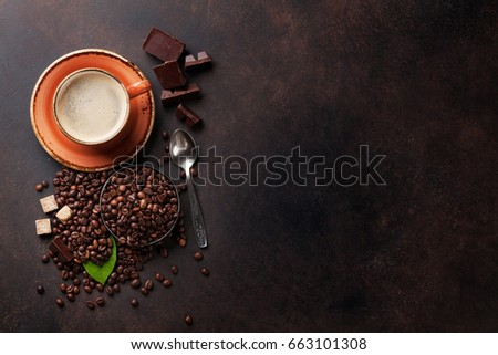 Coffee cup, beans, chocolate on stone background. Top view with copy space for your text #663101308