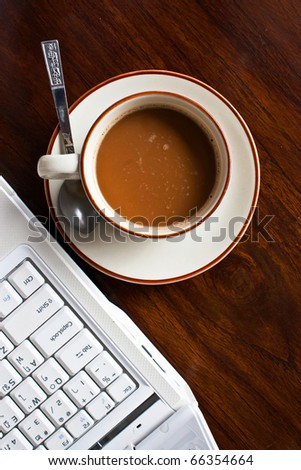 Coffee cup beside notebook on working table