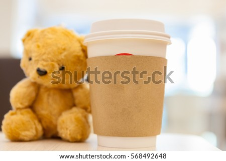 Coffee cup, blurred on teddy bear face in Blurred background with vintage filter