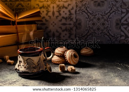 Coffee cup, books and cookies. Steaming coffee cup and traditional turkish coffee pot cezve. Cozy home atmosphere for reading and resting