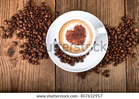 Coffee cup Cappuccino on old wooden table. Heart shape foam, top view.