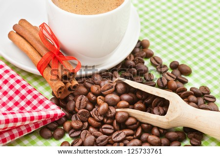 coffee cup, cinnamon sticks and coffee beans on kitchen table