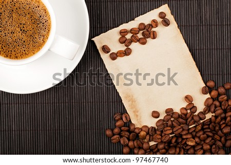 Coffee cup, coffee crops and handmade paper placed on bamboo coaster. Place for text.