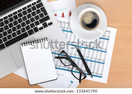 Coffee cup, laptop, notepad and glasses over papers with numbers and charts. View from above