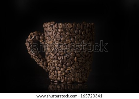 Coffee cup made of coffee beans on black background