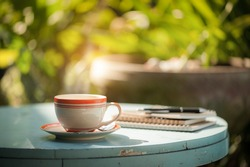 Coffee cup, notebooks, and pen on blue veteran table in morning time
