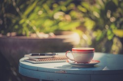 Coffee cup, notebooks, and pen on blue veteran table in morning time with vintage filter effect
