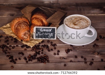 Coffee cup of cappuccino and coffee beans on brown wooden table #712766392