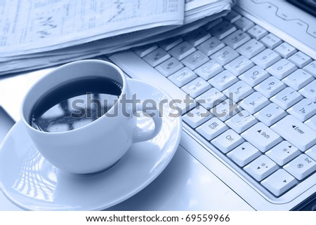 coffee cup on a newspaper near the laptop