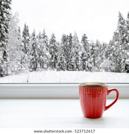 Coffee cup on a window sill. In the background, a beautiful winter forest in snow