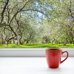 Coffee cup on a windowsill. Blooming apple tree outside the window