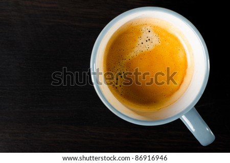 coffee cup on dark table, top view