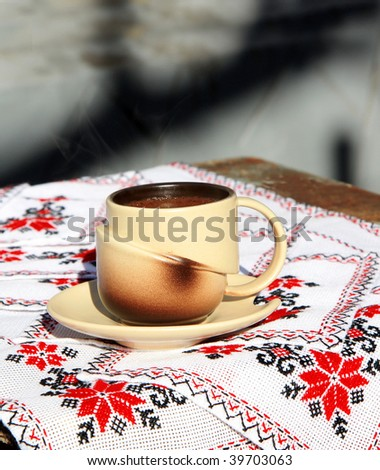 Coffee cup on embroidery tablecloth