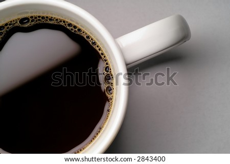 Coffee cup on grey background (seen from above) closeup