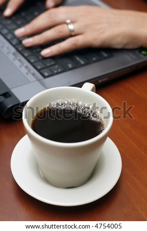 Coffee cup on table with hands and laptop in the background