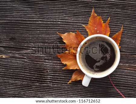 coffee cup on the autumn fall  leaves and wooden surface background