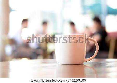 Coffee cup on the table with people in coffee shop as blur background