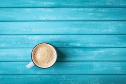 Coffee cup on turquoise wooden table top view.