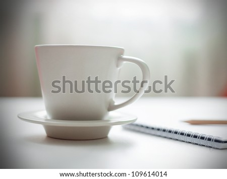 Coffee cup on white table, soft focus