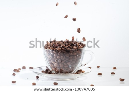 Coffee cup on with beans, on white background with falling beans