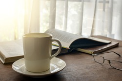 Coffee cup on wooden table by the window with opening book and eye glasses as background. Soft morning light shines through the curtain.