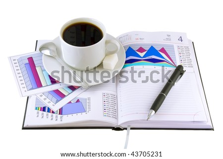 Coffee cup, pen, standing on the open personal organizer and  financial  diagrams  on a pages.Isolated.