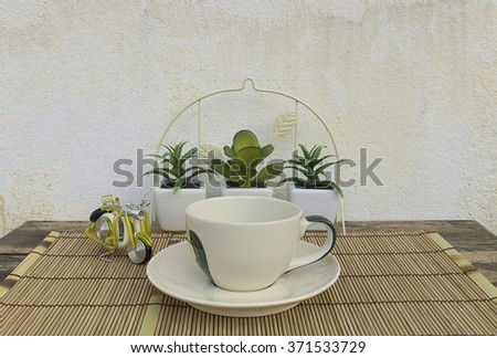 Coffee cup placed on a bamboo mat. Miniature motorcycles on the old wooden table. #371533729