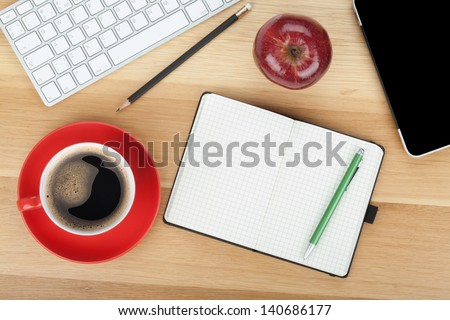 Coffee cup, red apple and office supplies on wooden table